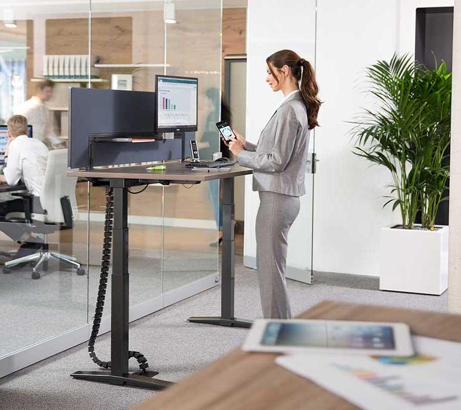 Frau steht an Schreibtisch